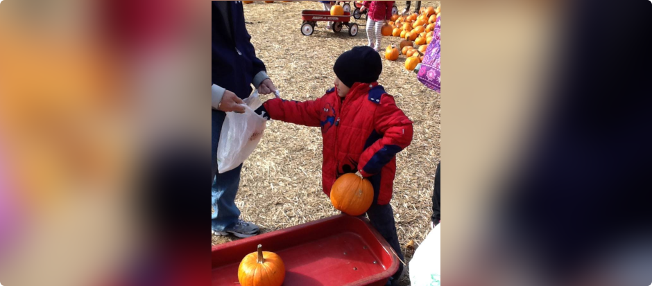 Kid carrying a pumpkin